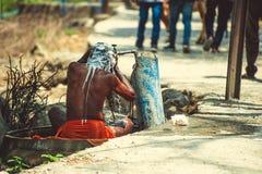 Sadhu wird unter fließendem Wasser nahe der Straße gewaschen lizenzfreies stockbild