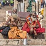 Sadhuen för två Shaiva, den heliga mannen sitter på ghatsna av Gangeset River i Varanasi, Indien Arkivfoton