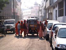Sadhus Around Rickshaw. This is a candid image of many Sadhus standing around a rickshaw in Shantikunj Haridwar India after a bandhara party. One using a very Royalty Free Stock Photo