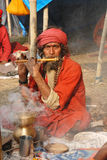 Sadhus, Holy Men of India. January 13, 2011-Ganga sagar, West Bengal, India –A saint performing flutefor the attraction- at the fair ground of Ganga sagar royalty free stock image