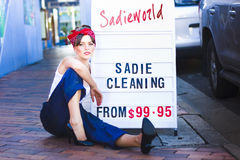 Sadie The Cleaning Lady. Marketing Her House Clean And Tidy Service While Sitting Next To A Sadieworld Advertising Sign On The Street Stock Image