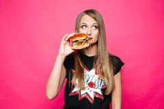 Sadly girl thinking eating tasty humburger or no. Front view of sadly young girl looking at side and thinking eating tasty humburger or no. Pretty woman wearing stock images