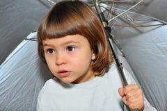 Sadly looks. Girl sadly looks outside under an umbrella Stock Image