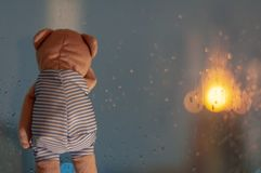 Sadly Teddy Bear crying at window in rainy day stock photo