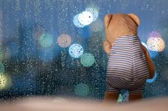Sadly Teddy Bear crying at window in rainy day royalty free stock photography
