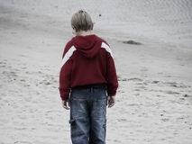 Sadness. Shot of a young boy on the beach royalty free stock photos