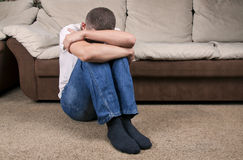 Sadness. Man sitting on the floor near the sofa and crying stock image