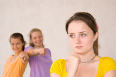 Sadness. Laughing friends and sad girl over uniform background Royalty Free Stock Photo
