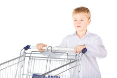 Sadness boy is standing near shopping basket Stock Images
