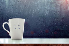 Sadness Coffee Mug with crying face cartoon inside the room, Blu stock photos