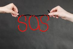 Two hands holding red SOS sign. Sadness, depression, troubles and very hard break up concept. Two hands holding red SOS sign Stock Image