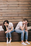Sadness girl and guy sitting on bed at home. Man and women in white T-shirts and blue jeans sitting on the bed . Concept of sadness family relationships Royalty Free Stock Images
