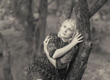 Sadness girl sitting on a tree branch Royalty Free Stock Photography