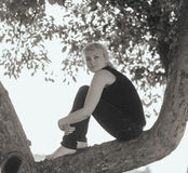 Sadness girl sitting on a tree branch Stock Images