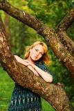 Sadness girl is on a tree branch Stock Images