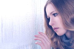 Sadness girl at the window in the rain Royalty Free Stock Photos