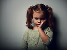 Sadness kid girl looking unhappy. Closeup portrait on dark Royalty Free Stock Image