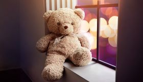 Sadness and Lonelyness Concept. Lonely Teddy Bear Toy Siting Alone beside Window in the Dark Room, City Night Light as Outside Vi. Ew stock images