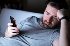 Sadness male portrait holding mobile phone alone. Man feeling depressed using phone at night stock images