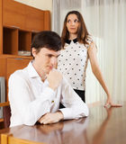 Sadness man against unhappy young woman. Family quarrel. Sadness men against unhappy young women at home Stock Images