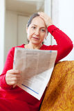 Sadness mature woman reading newspaper Stock Image