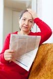 Sadness mature woman reading newspaper Stock Image