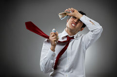 Sadness with money. Desperate young businessman with blowing necktie and his bunch of money. Recession and crisis concept Stock Images