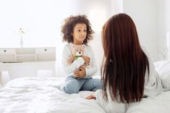 Upset girl holding her toy. Sadness. Nice sad curly-haired girl smiling and looking at her mom and her mother holding her toy Stock Photo