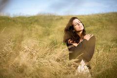 Sadness and nostalgia in nature. Sad shivery woman in brown sweater jacket hugging herself and walking in nature field on late summer cold day. Sadness Royalty Free Stock Images