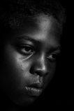 Sadness. A portrait of a young African American girl realizing the world she is growing up into.  A world still divided by hate.  Dark contrasts are used to set Royalty Free Stock Photos