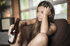 Sadness teen girl sits on sofa at home beer Stock Photography
