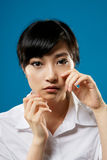 Sadness woman. Sadness, closeup portrait of Asian business woman on studio blue background Royalty Free Stock Images