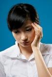 Sadness woman. Sadness, closeup portrait of Asian business woman on studio blue background Royalty Free Stock Photo