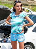 Sadness woman is standing near broken car. Sadness young brunette woman is standing near broken car Stock Photo