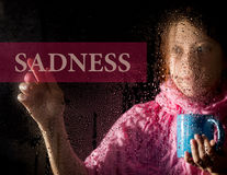 Sadness written on virtual screen. young woman melancholy and sad at the window in the rain, she holding a cup of hot Royalty Free Stock Image