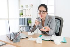 Sadness young female office worker catches cold. Feeling unwell during flu time and showing many medical pills looking at camera Stock Photography