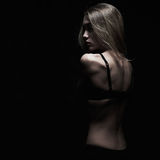 Sadness young woman with naked back over black background. Dark monochrome portrait of sexy body girl Royalty Free Stock Photo
