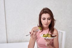 Sad women is on dieting time looking at broccoli on the fork. girl do not want to eat vegetables and dislike taste of Stock Photos