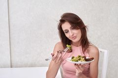 Sad women is on dieting time looking at broccoli on the fork. girl do not want to eat vegetables and dislike taste of. Sadwomen is on dieting time looking at Royalty Free Stock Photo