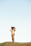 Safari boy. Young boy child playing pretend explorer adventure safari game outdoors with binoculars and bush hat stock photography