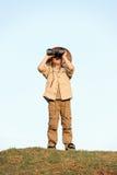Safari boy. Young boy child playing pretend explorer adventure safari game outdoors with binoculars and bush hat stock photos