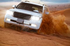 Safari on the car SUV through orange dunes in the desert. And blue sky background stock images
