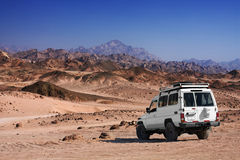 Safari in desert. Jeep in desert against Sinai mountains in Egypt Stock Photos