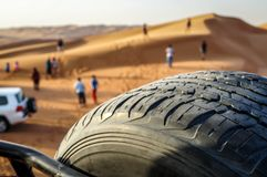 Safari in the desert sand dunes of Dubai. View from car with spare tire and with blurry background stock photography