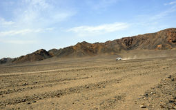 Safari jeep in the desert. A safari jeep traveling on a dirt road in desert - Egypt royalty free stock images