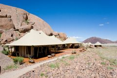 Safari camp in Africa luxury safari tents, Namibia. Safari tents in Wolwedans, Namibia, in front of huge boulders stock photos