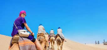 Safari tourism on camels. Sahara desert, Tunisia, North Africa. Group of tourists riding on camels. Safari tourism. Sahara desert, Tunisia, North Africa royalty free stock photos