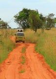 Safari Van rolling through Ugandan Savannah. A open top safari van rolls through the grass savannah of Murchison Falls National Park in Uganda stock photo