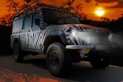 Safarijeep met een gestreepte patroonaandrijving door een droge hete savana van de aard van Afrika stock afbeeldingen