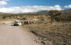 Safaris car. With tourist in the serengeti with clouds in the sky, you can see some mountains Stock Photo